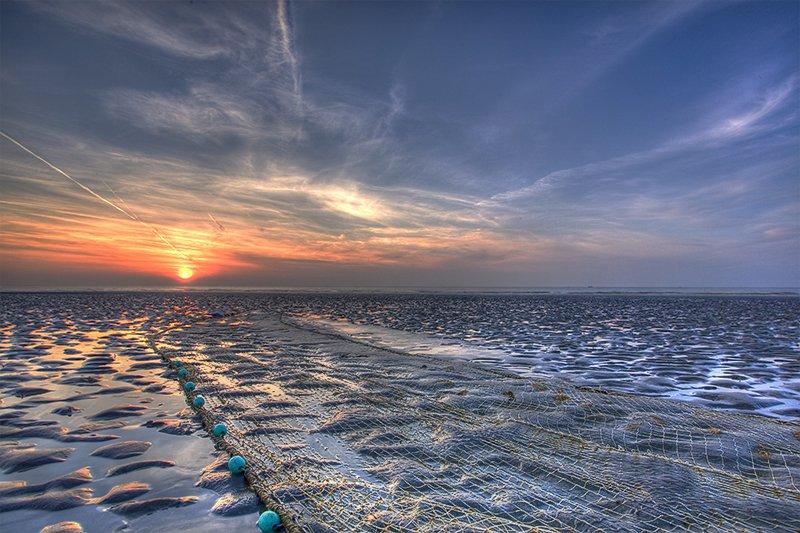 kuieren met zonsondergaan aan het strand Nieuwpoort